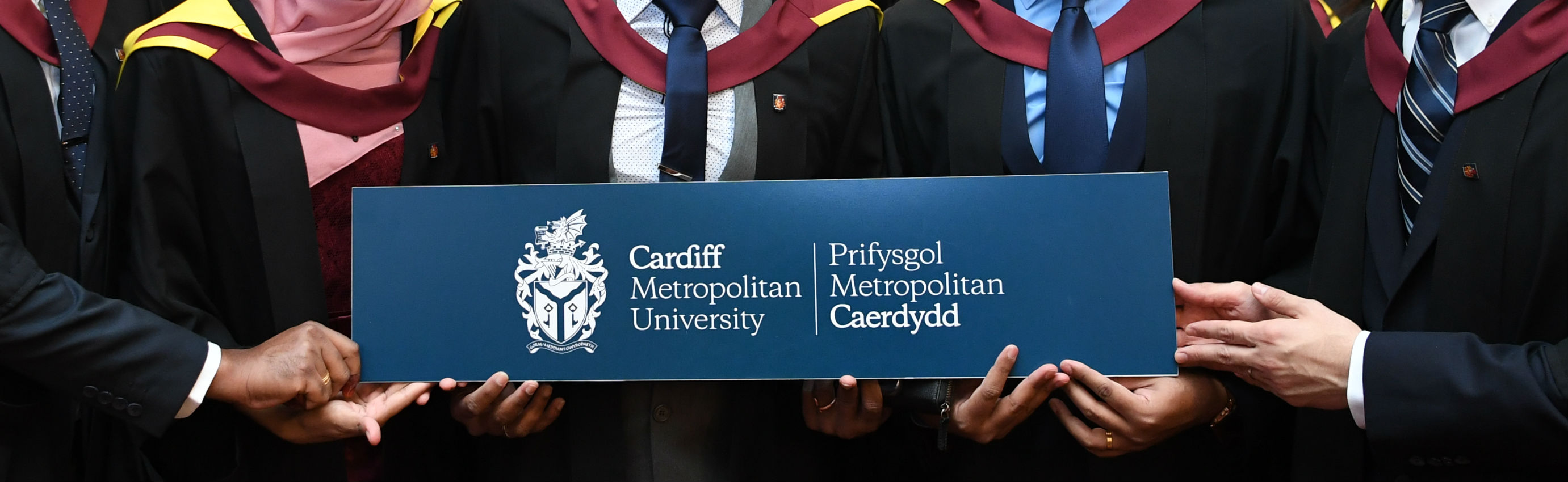 Graduates holding a sign with the university logo